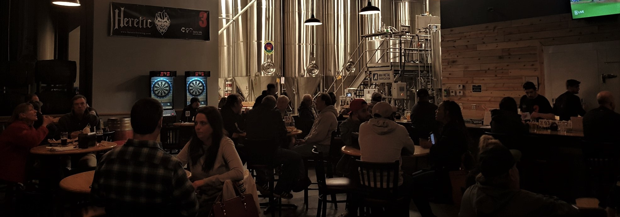Inside taproom shot with people drinking at tables and view of tanks in the background