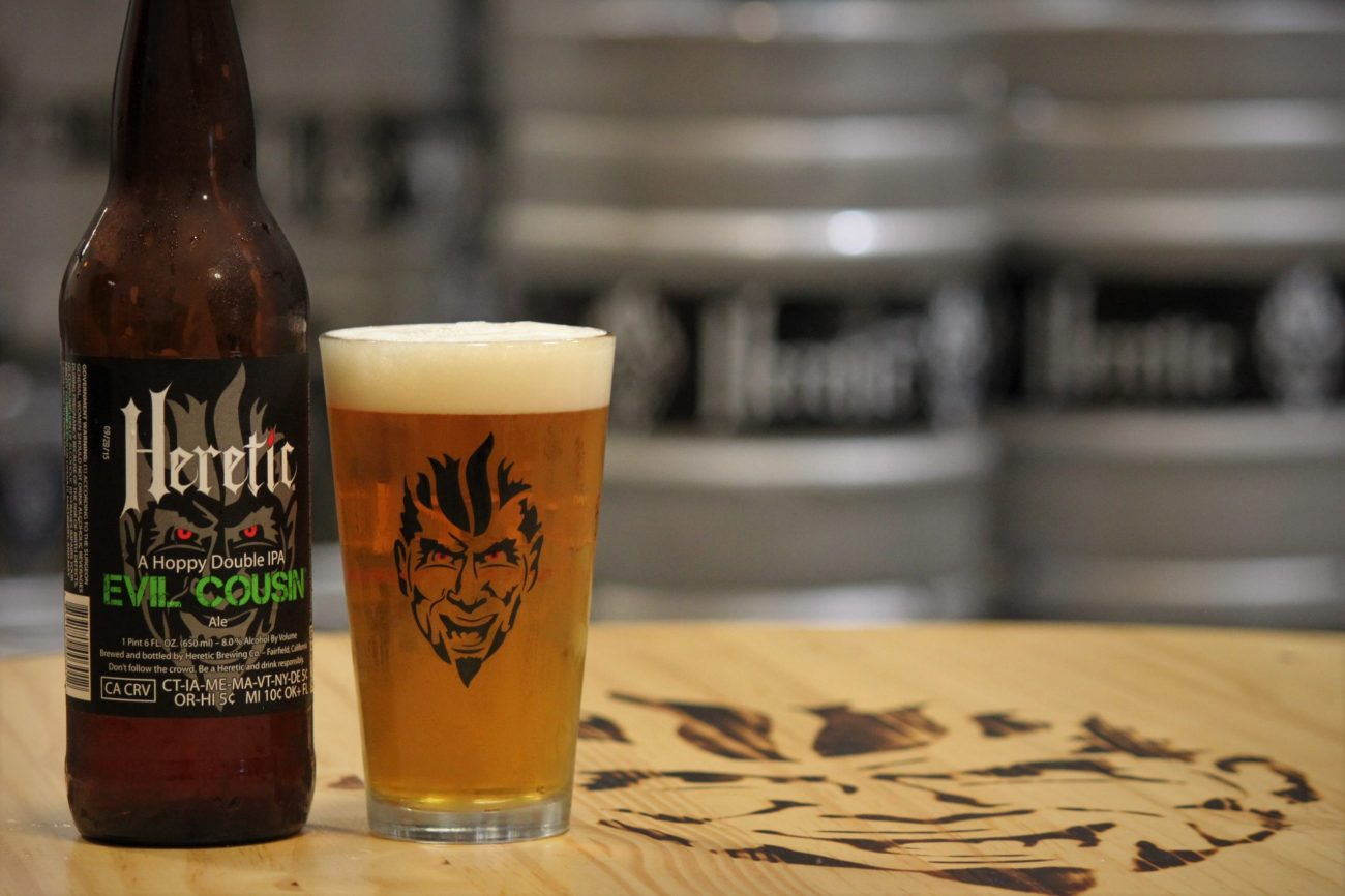 eVIL cOUSIN bEER POURED INTO GLASS ON TABLE WITH BURNT LOGO ON TOP